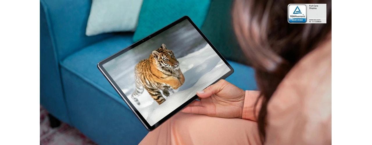 """Moteris, laikanti """"Lenovo Tab P11 Pro"""" ant kelių, žiūri tigro vaizdo įrašą"""